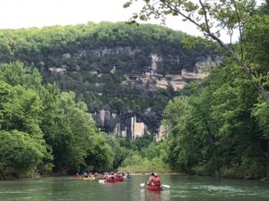A group of students paddle canoes down a river in Arkansas.